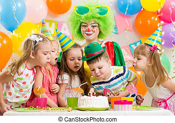 kids with clown celebrating birthday party and blowing candle on cake