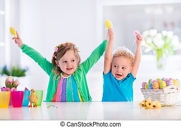 Kids with colorful Easter eggs - Kids painting colorful...