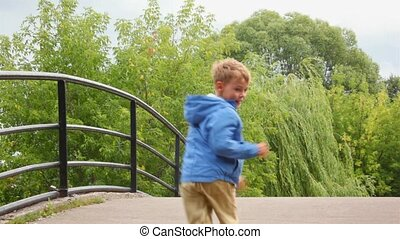 kids with dog running on bridge, from camera