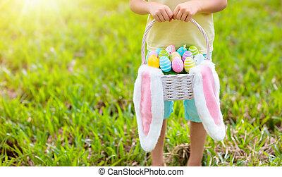 Kids with eggs basket on Easter egg hunt.