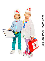 Kids with medical uniforms and toy doctor tools