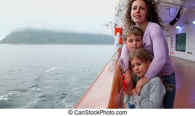 kids with mother stand on ship deck which sail near coastline