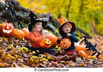 Kids with pumpkins on Halloween - Children wearing black and...