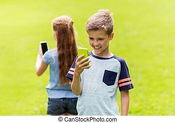kids with smartphones playing game in summer park -...
