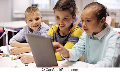 kids with tablet pc programming at robotics school -...