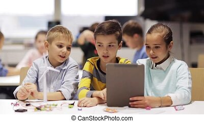 kids with tablet pc programming at robotics school - ...