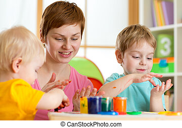 Kids with teacher painting in playschool