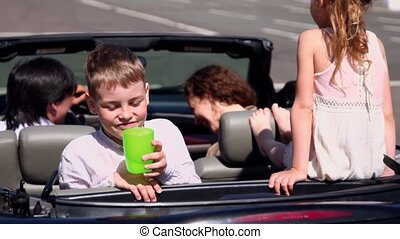 Kids with their parents sit in cabriolet and boy drinks