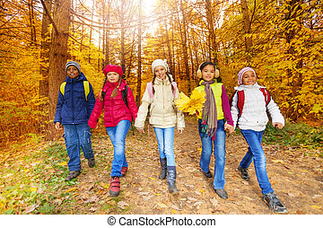 Kids with yellow maple leaves bunch walk in forest