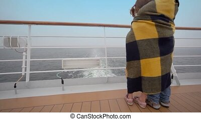 Kids wrapped in plaid stand on deck and admire seascape -...