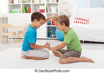 Kids wrestling on the floor - Kids wrestling and laughing on...