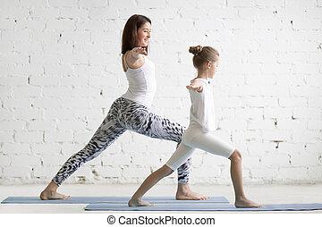 Kids yoga teacher training with a little girl Virabhadrasana...