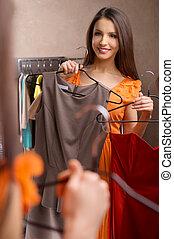 kies, dress., aantrekkelijk, jonge vrouw , vasthouden, jurken, in, haar, handen, en, kijken naar, de, spiegel