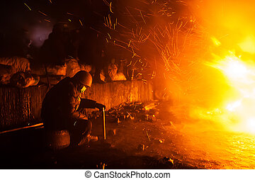 KIEV, UKRAINE - January 24, 2014: Mass anti-government protests in the center of the Ukrainian capital Kiev. Member of the Popular Resistance basking near the fire on Hrushevskoho St.