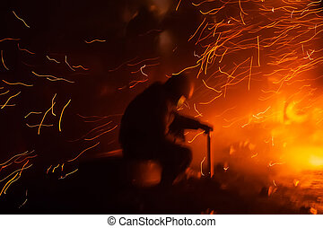 KIEV, UKRAINE - January 24, 2014: Mass anti-government protests in the center of the Ukrainian capital Kiev. Member of the Popular Resistance basking near the fire  on Hrushevskoho St.