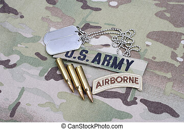 KIEV, UKRAINE - September 5, 2015. US ARMY airborne tab, flag patch, with dog tag and 5.56 mm rounds on camouflage uniform