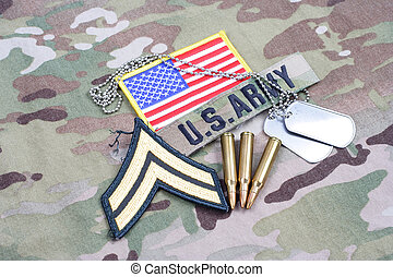 KIEV, UKRAINE - September 5, 2015. US ARMY Corporal rank patch, flag patch, with dog tag and 5.56 mm rounds on camouflage uniform