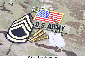KIEV, UKRAINE - September 5, 2015. US ARMY Sergeant First Class rank patch, flag patch, with dog tag with 5.56 mm rounds on camouflage uniform