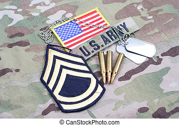 KIEV, UKRAINE - September 5, 2015 US ARMY Sergeant First Class rank patch, flag patch, with dog tag and 5.56 mm rounds on camouflage uniform