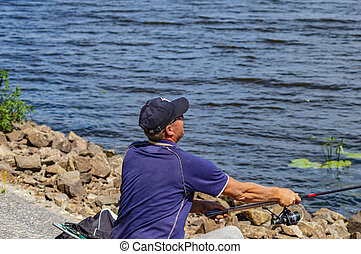 Kiev Ukraine, the Dnieper River 08/15/2016. Fisherman casts a spinning rod.