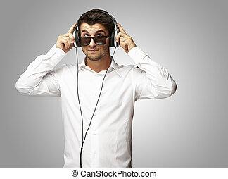 kihallgatás, felett, fejhallgató, fiatal, szürke, zene, háttér, portré, használ, ember