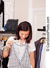 kijkende vrouw, op, jurkje, in, de opslag van de kleding