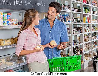 kijkende vrouw, op, man, terwijl, aankoop, kaas