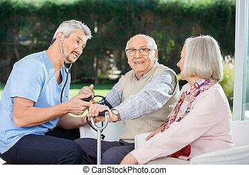 kijkende vrouw, op, mannelijke arts, het meten van bloeddruk