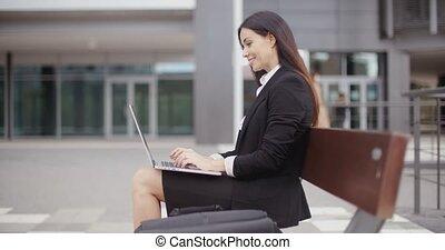 kijkende vrouw, op, met, draagbare computer, op, bankje