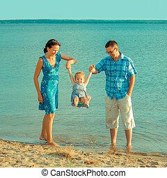 kilátás, közül, boldog, young család, having móka, képben látható, a, tengerpart., boldog, young család, alatt, egy, blue ruha, szórakozik, -ban, megüresedések, képben látható, gyönyörű, tengerpart