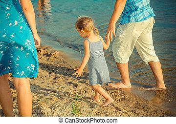 kilátás, közül, boldog, young család, having móka, képben látható, a, tengerpart., young anya, és, apuka, dabbles, noha, lány, a vízben, közel, a, shore.
