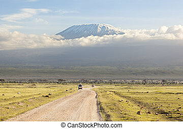 Kilimanjaro with snow cap seen from Amboseli National Park in Kenya with a road in the foreground.