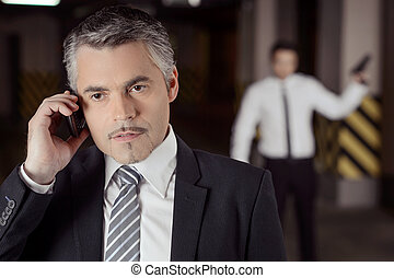 Killer and victim. Confident mature businessman talking at...