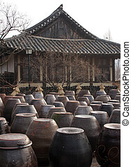 Kimchi pots in front of a traditional Korean home - Kimchi...