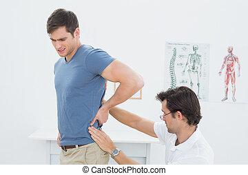 kinésithérapeute, équipe, examiner, dos, mâle, vue côté