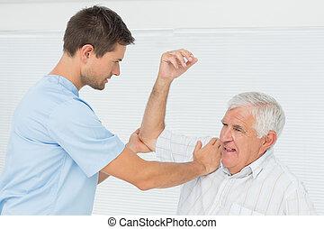 kinésithérapeute, Aider, sien, étendue, main, personne agee, homme