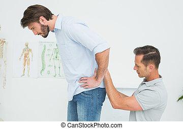 kinésithérapeute, examiner, dos, homme, mâle, vue côté