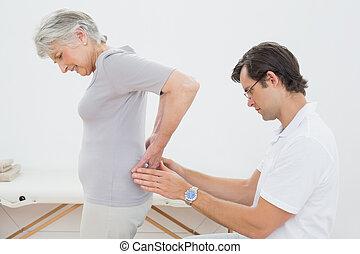 kinésithérapeute, personne agee, dos femme, examiner