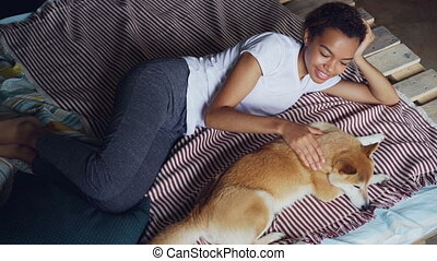 Kind African American girl is stroking lovely pet dog lying...