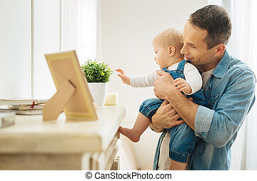 Kind attentive father showing his baby different items on the fireplace