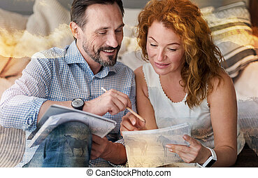 Kind attentive man helping his girlfriend to check her work