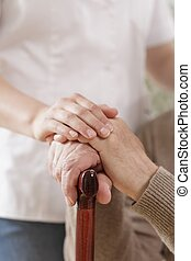 Kind caregiver holding senior man