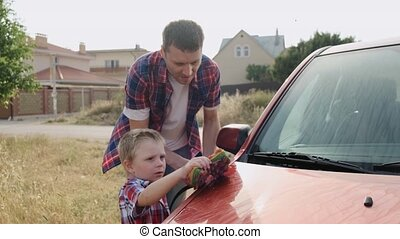 Kind caucasian dad patiently shows his son how to wash the...