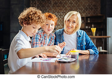 Kind elderly lady painting with grandsons at table