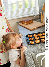 Kind girl standing in kitchen in front of the cookies