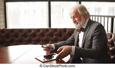 Kind grandfather spending his free time with tablet. - Kind...