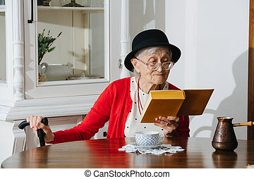 Kind grandmother is reading her book at dinner table at home.