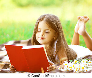 kind, het lezen van een boek, op het gras