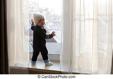 kind, in, een, warme, blauwe , jumpsuit, is, op, venster, in, winter