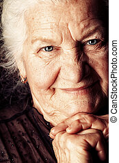 kind look - Portrait of a happy senior woman smiling at the ...